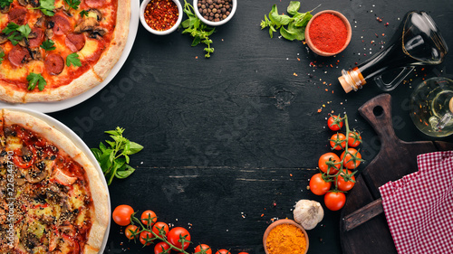 A set of Italian pizza. Italian cuisine. On a black wooden background. Free copy space. Top view.