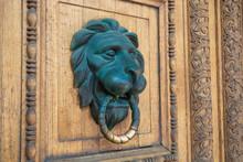 Bronze Door Knocker In The Form Of A Lion's Head On A Wooden Door