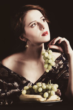 Portrait Of Beautiful Rich Woman With Grapes.
