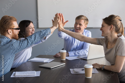 Photo  Excited happy business team of employees or partners group giving high five duri