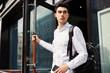 Trendy businessman walking out of doorway
