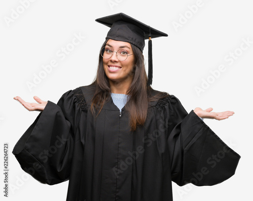 b848313bd7c Young hispanic woman wearing graduated cap and uniform clueless and  confused expression with arms and hands raised. Doubt concept.
