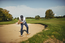 Senior Golfer Trying To Chip Out Of A Bunker
