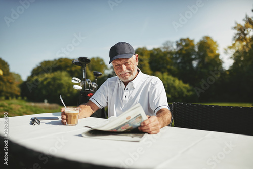 Tablou Canvas Smiling senior man drinking coffee after a round of golf