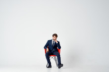 Man In A Suit Sitting On A Red...