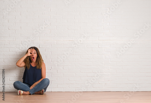 Fototapety, obrazy: Middle age hispanic woman sitting on the floor over white brick wall doing ok gesture shocked with surprised face, eye looking through fingers. Unbelieving expression.