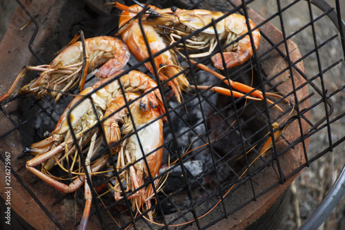 Thai people cooking grill shrimp or prawn on stove