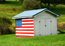 An Outbuilding Or Shed With The American Flag Painted On The Side.