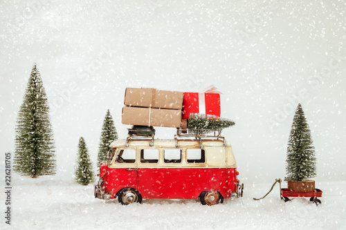Vintage Merry Christmas postcard background - Miniature antique car carrying presents (gift box) on roof and christmas tree in snowy winter forest.