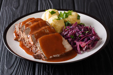German Food Sauerbraten - Slowly Stewed Marinated Beef With Gravy With Potato Dumplings And Red Cabbage Close-up On A Plate. Horizontal