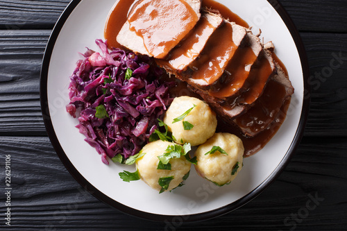 German roast pot Sauerbraten served with potato dumplings and red cabbage close-up. horizontal top view