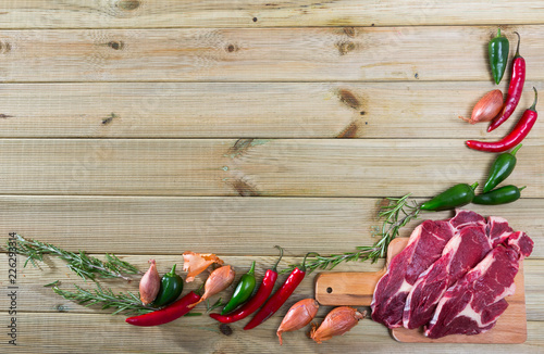 Raw beef with fresh vegetables on wooden background