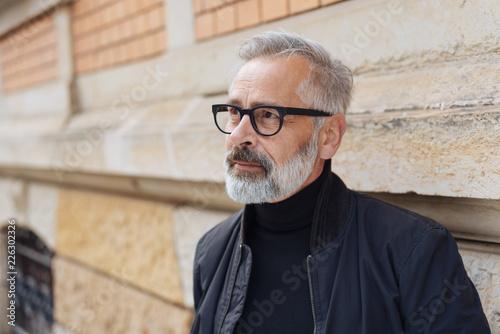 Fotomural  nachdenklicher, grauhaariger mann steht draußen vor dem haus