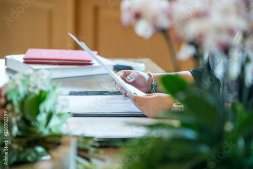 Tuinposter Restaurant a woman sitting at a desk and holding some documents, on the desk there are flowers and various docuaries and books