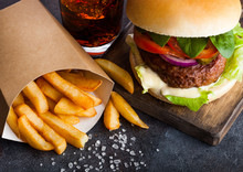 Fresh Beef Burger With Sauce And Vegetables And Glass Of Cola Soft Drink With Potato Chips Fries On Stone Kitchen Table Background. Macro