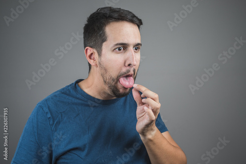 Fotografie, Tablou  man pulling something out of his tongue with a face of disgust