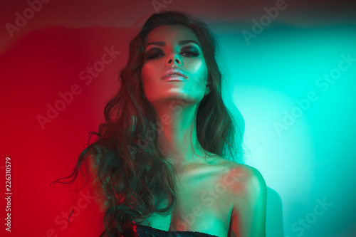 Spoed Foto op Canvas Beauty Fashion model brunette woman in colorful bright neon lights posing in studio. Beautiful sexy girl, trendy glowing makeup, metallic silver lips