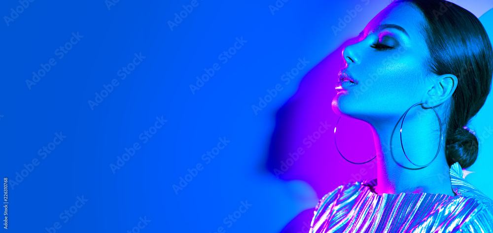 Fototapeta Fashion model brunette woman in colorful bright neon lights posing in studio. Beautiful sexy girl, trendy glowing makeup, metallic silver lips