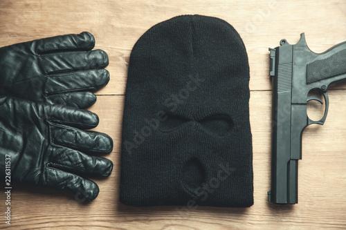 Pinturas sobre lienzo  Pistol, balaclava and gloves on wooden background
