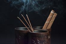 Burning Incense Sticks And Brown Bowl On Black Background. Beautiful Smoke From Above