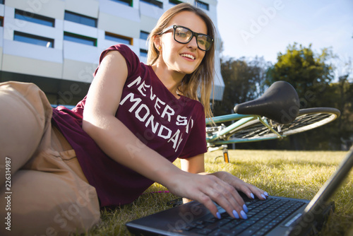 Fotografie, Obraz  Pretty student woman wearing glasses lying near the university and typing on the