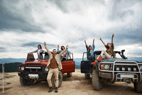 Positive young people resting on off-road vehicles while spending an active weekend in the mountains