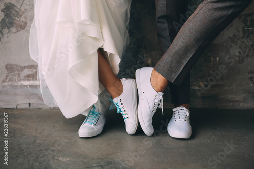 Hipster couple standing together wearing white sneakers. Wedding in sneakers, love. Soft focus tehnic, wedding style clothes