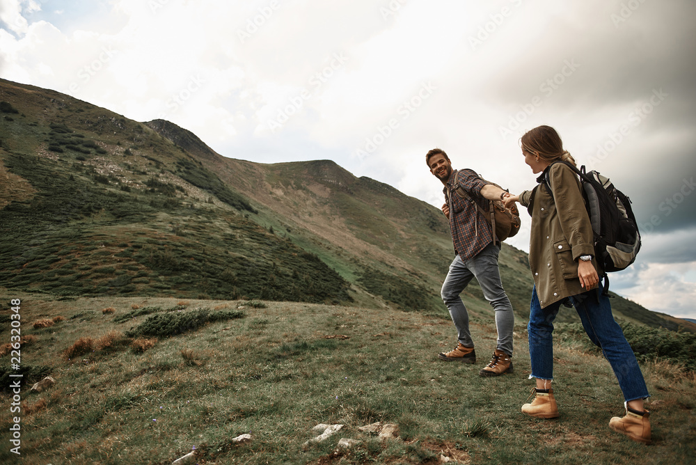 Fototapety, obrazy: Holding hands. Cheerful happy young traveler smiling and feeling glad while traveling with his pretty girlfriend and giving her his hand on the hill