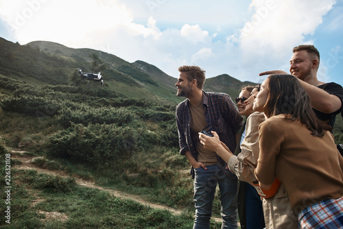 Funny dron. Positive emotional young people traveling in the mountains and using modern little dron