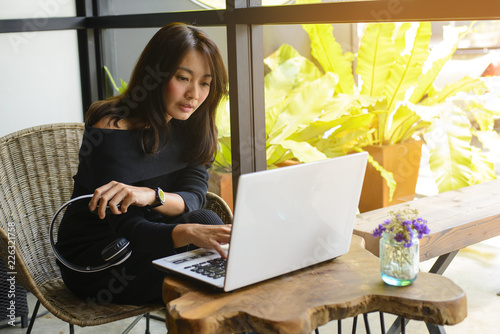 Young woman working with laptop sitting in a cafe