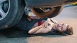 Sexy mechanic girl lying under the car and fixing it in slow motion
