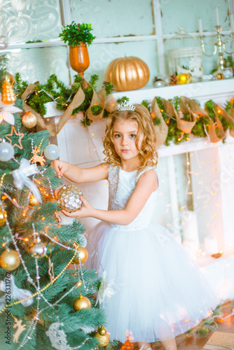 Tuinposter Sprookjeswereld Cute little girl with curly blond hair at home near a Christmas tree with gifts and garlands and a decorated fireplace