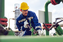 Worker Adjusting Gauge At Oil ...