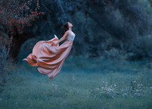 A Young Woman, A Mysterious Witch Is Floating In The Air Like A Butterfly. A Luxurious, Long Dress Flutters In The Wind In Flight. Cold Forest Background. Enchanted Princess. Art Photo Of Levitation