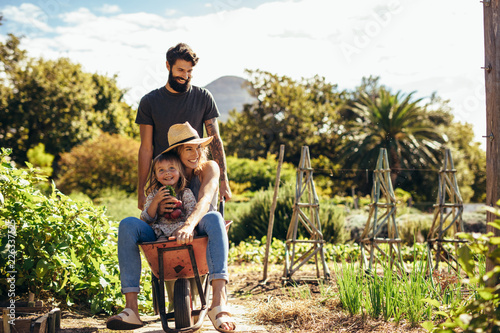 Photographie Father gives mother and daughter ride in wheelbarrow