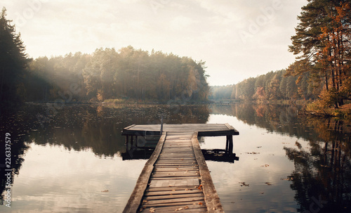 Foto auf Leinwand Grau The Breath Of Autumn. Autumn foliage and fog lake in morning with boat dock