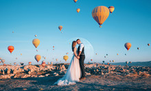 Bride And Groom On The Background Of The Moon And Balloons Flying Over The Valley Of Love