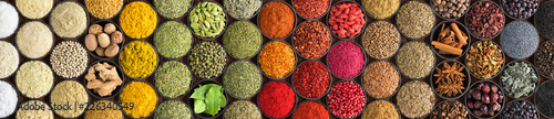 Various spices and herbs as a background. Colorful condiments in cups, top view