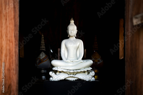 Tuinposter Boeddha white buddha statue in thai lanna temple with soft-focus and over light in the background
