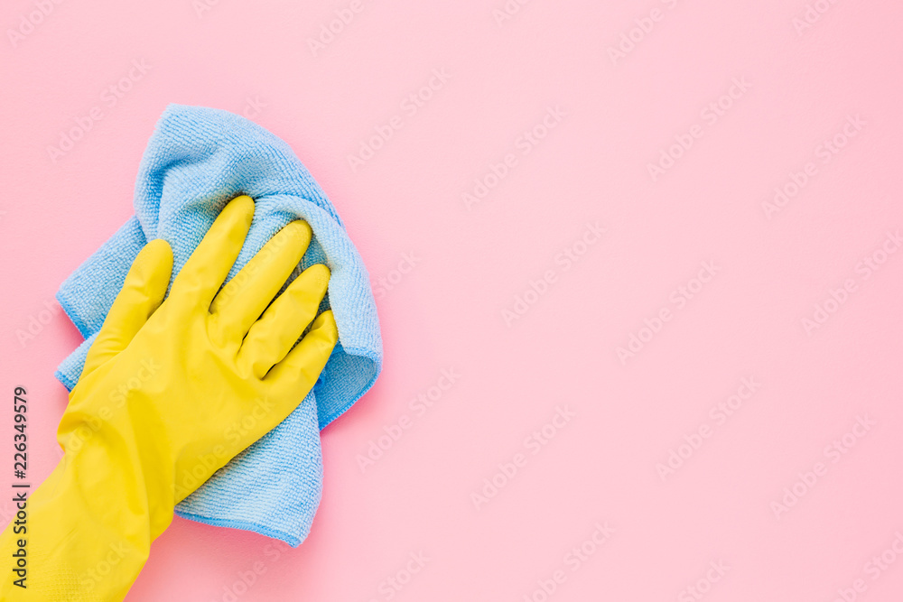 Fototapety, obrazy: Employee hand in yellow rubber protective glove wiping pastel pink wall from dust with blue dry rag. General or regular cleanup. Commercial cleaning company. Copy space. Empty place for text or logo.