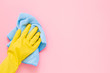 canvas print picture - Employee hand in yellow rubber protective glove wiping pastel pink wall from dust with blue dry rag. General or regular cleanup. Commercial cleaning company. Copy space. Empty place for text or logo.