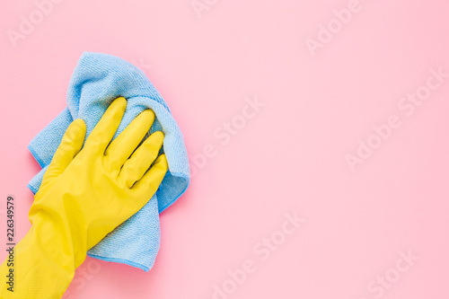 Employee hand in yellow rubber protective glove wiping pastel pink wall from dust with blue dry rag Fotobehang