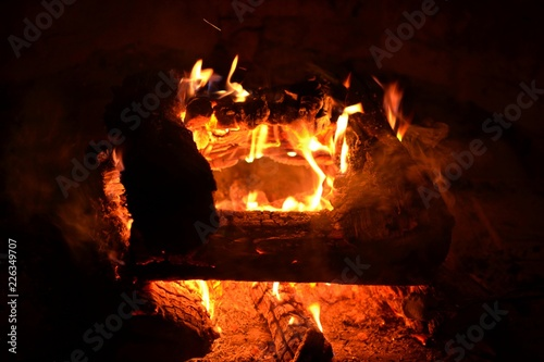 Camp fire in a fire pit with glowing embers and flames