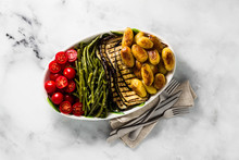 A Side Dish Of Vegetables On The Holiday Table. Healthy Food For The Whole Family Or Dinner At A Restaurant On A White Marble Table. Baked Potatoes, Grilled Eggplants, Cherry Tomato Salad