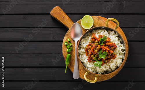 Fényképezés  vegan curry with green peas and basmati rice served on a wooden table tray, heal