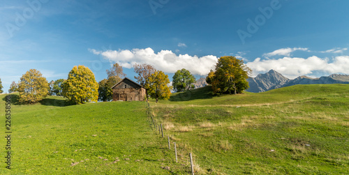 Tuinposter Pistache old wooden barn and mountain landscape in autumn in SwItzerland