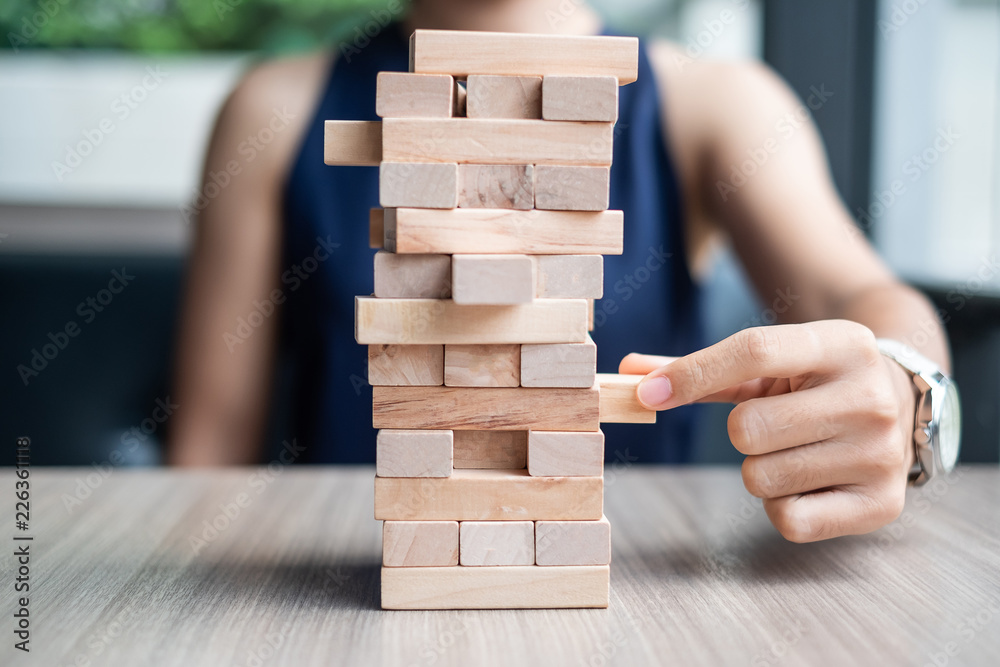 Fototapeta Businesswoman hand placing or pulling wooden block on the tower. Business planning, Risk Management, Solution and strategy Concepts