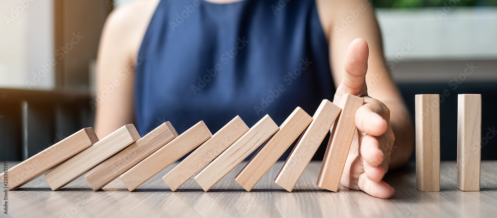 Fototapeta Businesswoman hand Stopping Falling wooden Dominoes. Business, Risk Management, Solution and strategy Concepts