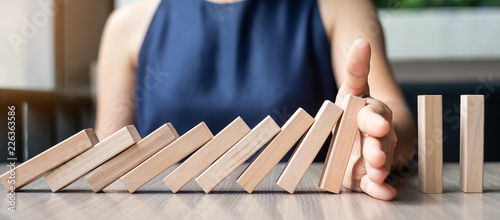 Obraz na plátně  Businesswoman hand Stopping Falling wooden Dominoes