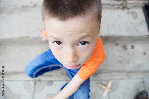 Fotografie, Obraz  top view boy portrait close-up sitting on stairs